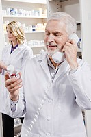 Pharmacist holding pill bottle and talking on telephone