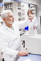 Pharmacist pouring pills into counting machine (thumbnail)