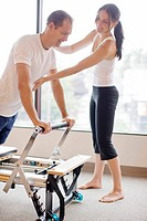 Personal trainer guiding man on pilates equipment