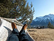 Detail of mans legs while lying in hammock alpine meadow and Three Sisters Mountain behind above Canmore Canada Alberta