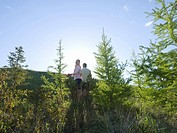Couple walking up slope of alpine larch in early spring into sunlight Canada Alberta