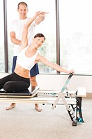 Personal trainer guiding grimacing woman on pilates equipment