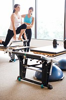 Native American personal trainer guiding woman on pilates equipment
