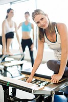 Portrait of smiling woman sitting on pilates equipment