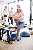 Portrait of smiling woman on pilates equipment