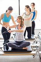 Personal trainers guiding women on pilates equipment