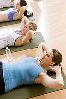 Women on exercise mats doing sit_ups