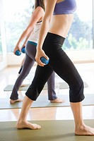 Side view of women working out with weight balls in exercise class