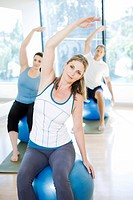 People on exercise balls stretching arms