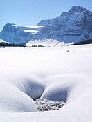 Partly snow covered mountain creek in alpine meadow and distatnt snowy mountains Canada Alberta Banff National Park