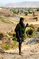 Shepherd stands barefoot in arid landscape near Bahir Dar Ethiopia