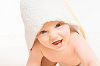 A smiling baby wearing a towel.