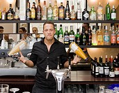 Portrait of bartender spinning drinks