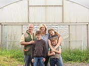 Farmer And Family Outside Polytunnel