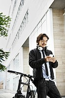 Man next to bicycle, headphones on