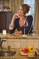 Young happy Caucasian woman with wine glass in kitchen