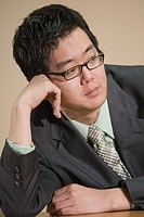 Young Asian businessman leaning on conference table, looking away