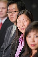 One Caucasian and three Asian businesspeople in a row, focus on woman in middle
