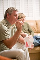 Portrait of father and teenage son eating Chinese takeout in living room