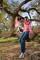 Portrait of African American mother and daughter sitting on tree branch in park, looking at camera