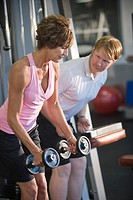 Mature woman lifting weights at gym with personal trainer helping