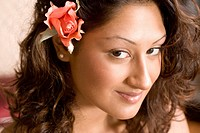 Close_up portrait of young Indian woman with flower in her hair, looking at camera