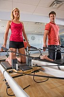 Portrait of young woman and young man on Pilates exercise equipment in gym with mirror in background