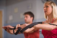 Young woman and young man sitting on Pilates exercise equipment in gym