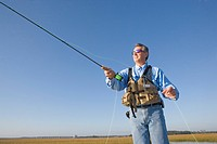 Mature adult man in sunglasses casting fishing pole in river