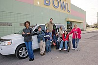 Portrait of multi_ethnic teenagers and women standing next to mini van in bowling alley parking lot