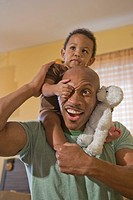 Portrait of happy African American father holding son on shoulders indoors, looking at camera