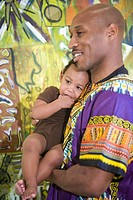 Portrait of happy African American father dressed in traditional African attire holding son indoors, looking at camera