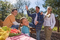 Young happy family playing at picnic table near campsite