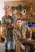 Portrait of senior man holding child and mid adult man in garage next to tools