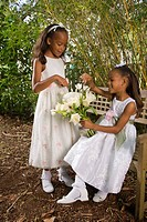 Happy African American flower girls sitting on garden bench pointing at flowers in the bridal bouquet
