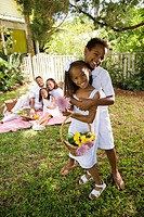 Portrait of happy African American young brother and sister hugging in front yard with rest of family in background