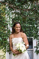 African American bride posing outside with bridal bouquet on wedding day