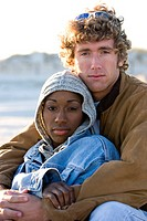 Portrait of young interracial couple sitting on beach with arm around