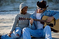 Young interracial couple sitting at beach, man playing guitar