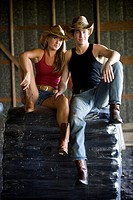Portrait of young couple wearing cowboy hats, sitting on bags of fertilizer in a barn