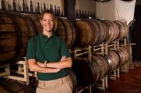 Winery tour guide posing beside wine barrels