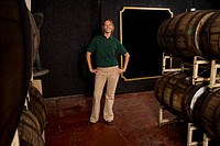 Winery tour guide posing beside wine barrels