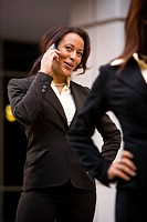 Multiracial businesswoman talking on mobile phone outside office building