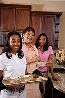 Portrait of mother/grandmother and teenage daughters baking cookies in kitchen