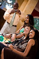 Two African American teenage girls sitting with mother/grandmother in living room with father/grandfather holding camera
