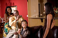 Two African American teenage girls with mother/grandmother in living room with father/grandfather holding camera