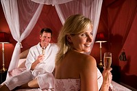 Romantic couple in bed drinking champagne