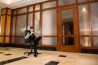 Portrait of young businessman sitting on office chair alone in lobby