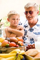 Young boy sitting on grandfather´s lap at table with fruits