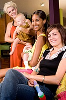 Portrait of young mothers holding babies in living room